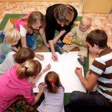 Große glückliche Familie, die zusammen ein Inneres zeichnet Stockbilder