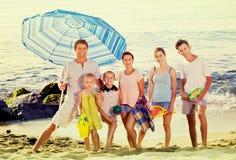 Große lächelnde Familie, die zusammen auf Strand am Sommertag steht Stockbild