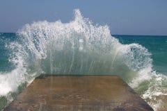 Große Meereswellen, die auf einem Wellenbrecher brechen Lizenzfreie Stockfotografie