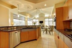 Große moderne hölzerne Küche mit Wohnzimmer und hoher Decke. Stockbilder
