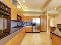 Große moderne hölzerne Küche mit Wohnzimmer und hoher Decke. Stockfotos