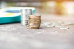 Groeiende muntstukken en calculator op houten lijst met groen Royalty-vrije Stock Foto
