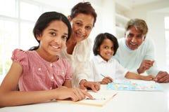Großeltern, die Kindern mit Hausarbeit helfen Lizenzfreies Stockbild