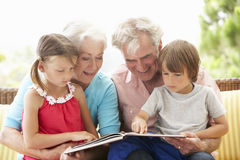 Großeltern-und Enkelkind-Lesebuch auf Garten Seat Stockbild