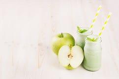 Groen appelfruit smoothie in glaskruiken met stro, muntbladeren, appelen Witte houten raadsachtergrond, exemplaarruimte Royalty-vrije Stock Foto