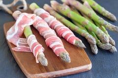 Groen asperge en bacon op houten raad, donkere leiachtergrond, ingredi?nten voor gezond horizontaal voorgerecht, royalty-vrije stock afbeelding