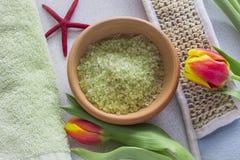 Groen badzout in een kom en Kuuroordfaciliteiten voor ontspanning royalty-vrije stock afbeelding