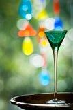 Groen cocktailglas met kleurrijke achtergrond Stock Afbeeldingen