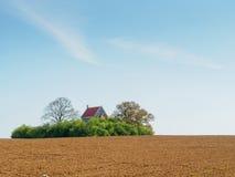 Groen die eiland door bomen en weinig oude kerk wordt gecreeerd Royalty-vrije Stock Afbeeldingen