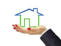 Groen die huis in vrouwenhand op witte achtergrond wordt geïsoleerd. Royalty-vrije Stock Afbeeldingen