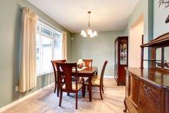 Groen eetkamerbinnenland met klassiek bruin meubilair. Stock Foto's