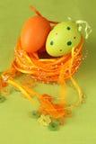 Groen en oranje Paasei in een nest Stock Fotografie