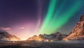 Groen en purper aurora borealis over sneeuwbergen stock foto