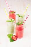 Groen en rood fruit smoothie in glaskruiken met stro, muntbladeren, aardbei en appelen Stock Foto
