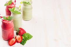 Groen en rood fruit smoothie in glaskruiken met stro, muntbladeren, aardbei en appelen Witte houten raadsachtergrond, exemplaarku Stock Foto's