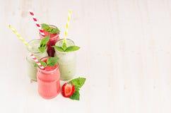 Groen en rood fruit smoothie in glaskruiken met stro, muntbladeren, aardbei en appelen Witte houten raadsachtergrond, exemplaarku Royalty-vrije Stock Fotografie