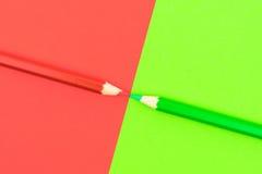 Groen en Rood gekleurd potloden en document Stock Foto's