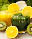 Groen en sinaasappel smoothies Stock Foto's