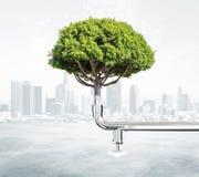 Groen energieconcept met boom en waterkraan bij stadsachtergrond Stock Afbeeldingen