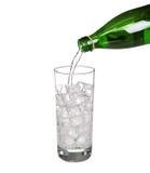Groen flessen gietend water in sprankelend glas van koud mineraal royalty-vrije stock foto