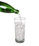 Groen flessen gietend water in sprankelend glas van koud mineraal royalty-vrije stock foto's