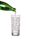 Groen flessen gietend water in sprankelend glas van koud mineraal stock afbeelding