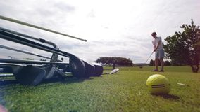 Groen gazon met clubs en een mannelijke speler die een schot nemen stock footage