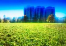 Groen gazon met drie onscherpe gebouwenachtergrond stock afbeelding