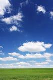 Groen gebied, blauwe hemel en witte wolken Stock Foto's