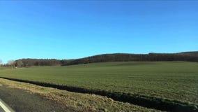 Groen gebied tegen heuvels met bomen in de vroege lente Weergeven van het bewegen van autoraam stock video