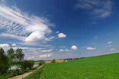 Groen gebied, weg, blauwe hemel en witte wolken stock foto's
