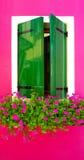 Groen houten verfvenster in Burano met heldere roze kleur stock fotografie