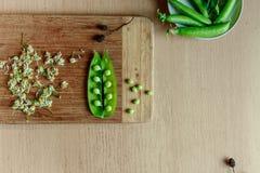 Groen koord van erwten op houten keuken stock afbeeldingen