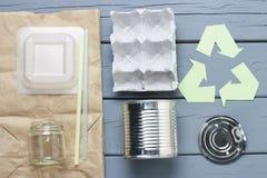Groen kringloophuisvuilsymbool en plastiek, ijzerhuisvuil, karton op een grijze achtergrond, hoogste mening stock foto