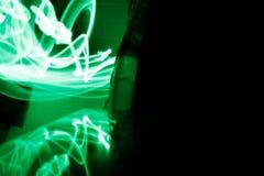 Groen licht het schilderen fotografie - krommen en golven van neon groen licht tegen een zwarte achtergrond stock foto's