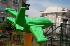Groen plastic vliegtuig op de speelplaats stock foto's