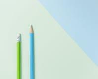 Groen potlood en blauw potlood op groene en lichtblauwe achtergrond Stock Afbeeldingen