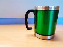 Groen roestvrij staal groen glas met zwart handvat op de houten lijst met blauwe muurachtergrond en exemplaarruimte stock foto