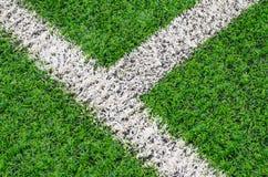 Groen synthetisch grassportterrein met witte lijn stock foto