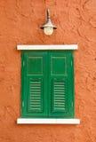 Groen venster op oranje muur Royalty-vrije Stock Foto's