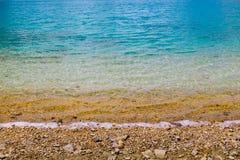 Groenachtig blauwe water overzeese oceaanachtergrond met kiezelstenen Stock Afbeeldingen