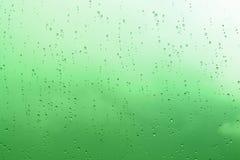 Groene abstracte waterdalingen op de glasachtergrond Stock Afbeeldingen
