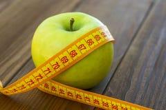 Groene appel met het meten van band op houten achtergrond Appelen en het naaien meetlint op een houten lijst Om gewicht te verlie stock foto