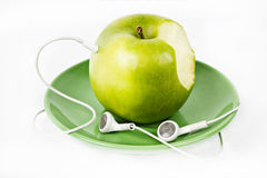 Groene Appel met Hoofdtelefoons op groene plaat Stock Fotografie