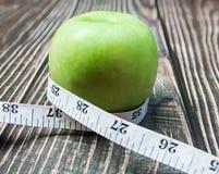 groene appel met meting op het hout stock foto's