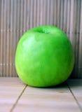 Groene appel op de bamboeachtergrond Stock Afbeeldingen