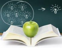 Groene appel op een boek Stock Afbeeldingen