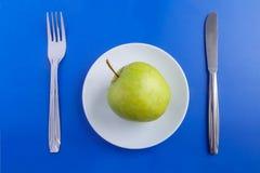 Groene appel op een schotel, met een vork en een mes stock foto