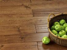 Groene appelen in een mand op een eiken parket Stock Afbeeldingen