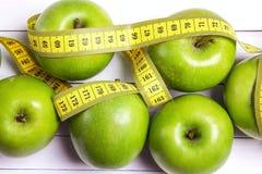 Groene appelen en gele centimeterband op witte houten backgrou stock afbeelding